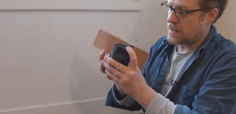 Fitting a strip of sandpaper to a sanding block